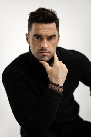 Portrait of handsome man in black turtleneck jumper isolated on white background