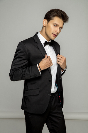 Handsome man wear balck suit with bow tie, isolated on gray background