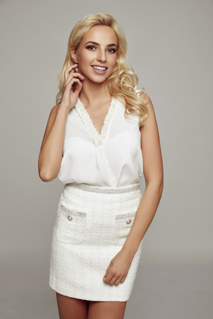 Beautiful blonde smiling young woman wear white top and skirt isolated on gray background