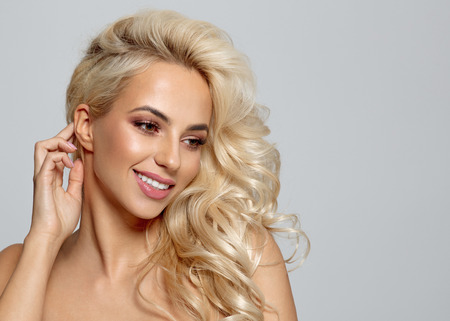 Blonde beautiful woman with healthy skin looking at copy space and smiling
