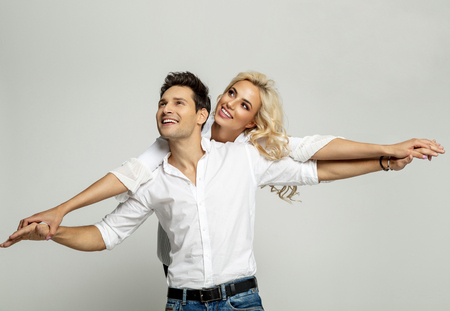 Beautiful happy couple doing airplane with their arms and looking at empty space isolated over gray background