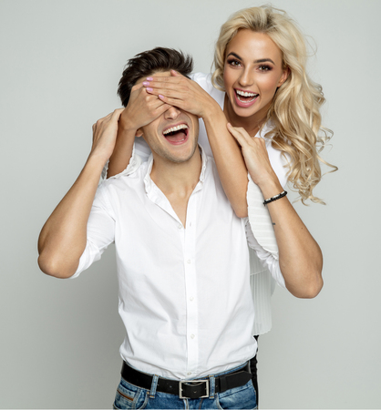 Portrait of a happy young couple, woman covering her boyfriends eyes isolated over gray background