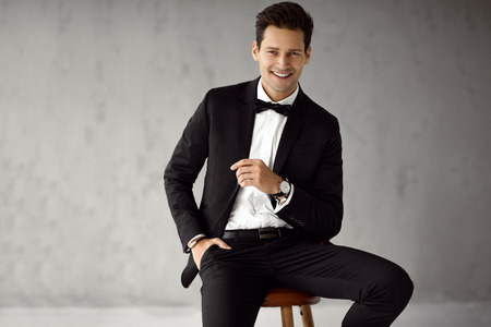 Young handsome man in black suit with copy space