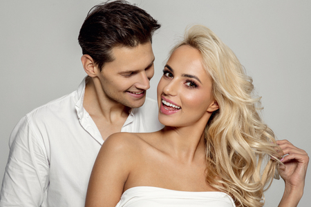 Portrait of attractive young smiling couple isolated over gray background Stockfoto