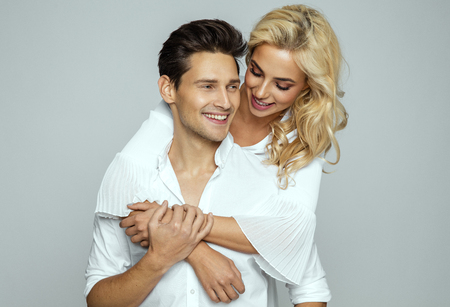Image of lovely couple having fun while man piggybacking his girlfriend isolated over gray background Stockfoto