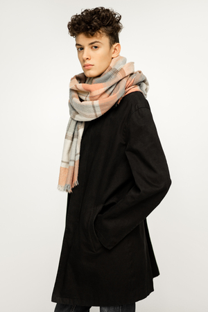 Handsome young man wearing black long trench coat and scarves