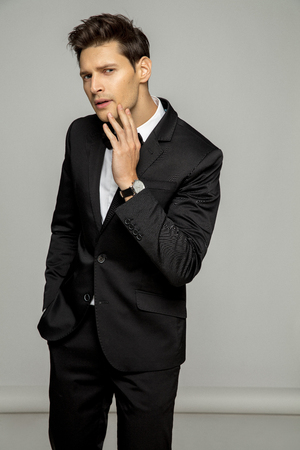 Handsome man in black suit over gray background