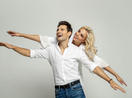 Handsome man is holding his gilrfriend on his back looking at empty space and keeping arms outstretched isolated over gray background