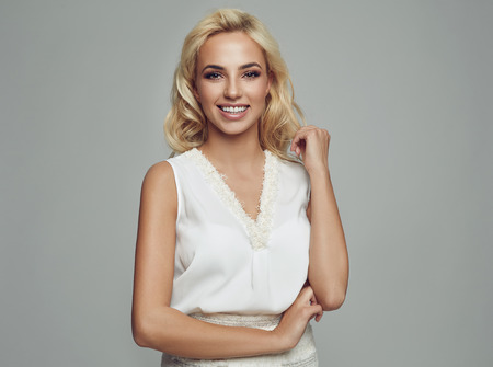 Beautiful blonde smiling woman wear white top isolated on gray background