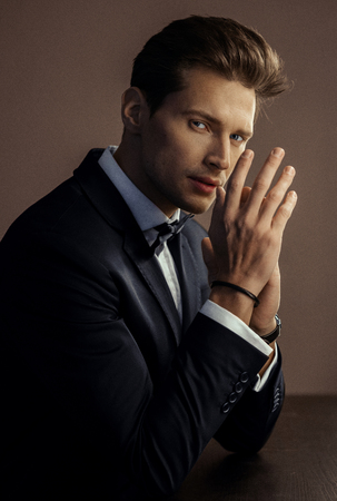 Portrait of handsome man in black suit rubbing his hands and looking at camera