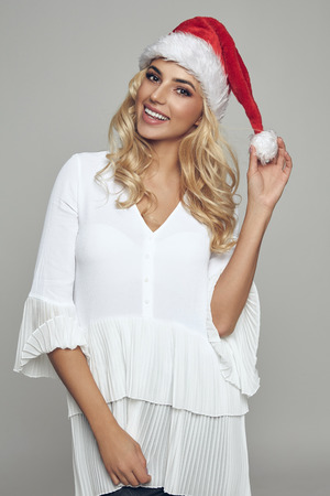 Beautiful blond smiling woman wear santa claus hat isolated on gray background