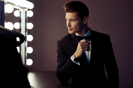 Sexy man in black suit looking at mirror in wardrobe