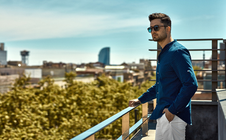 Handsome man in summer time looking on city view
