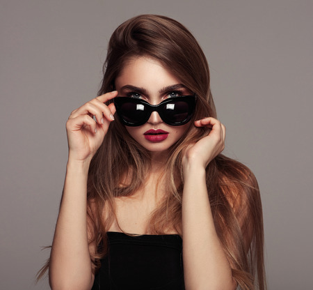 Portrait of young woman with long hair wear sunglasses isoalted over gray background Stockfoto