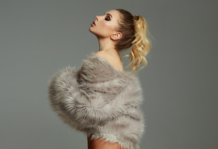 Blonde sexy woman in faux fur isolated on gay background 写真素材 - 124946619