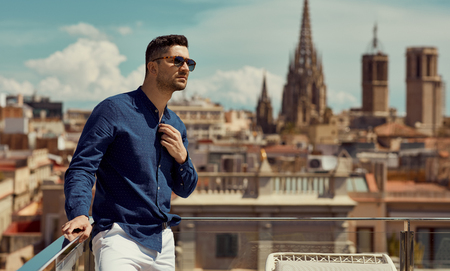 Portrait of handsome man wear sunglasses and standing against the background of the Barcelona