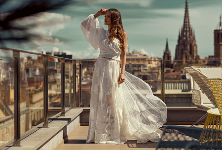 Beautiful young bride in white wedding dress posing outdoor over city view