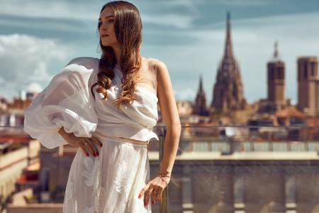 도시 풍경에 야외 포즈를 취하는 젊은 여성 모델의 사진