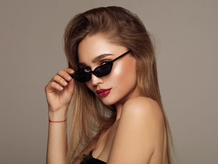 Portrait of young woman wear sunglasses with copy space isoalted over gray background