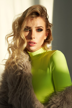 Fashion portrait of young attractive blonde woman wear faux fur posing during the sunset
