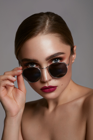 Portrait of young girl wear sunglasses isolated over gray background