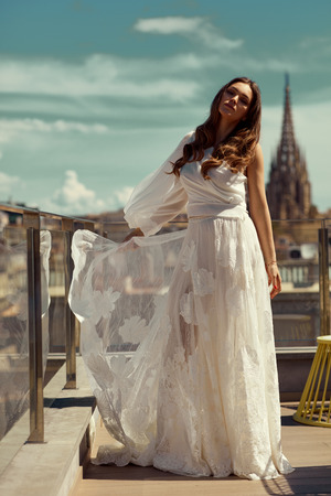 Beautiful bride in white dress posing outdoor over city view
