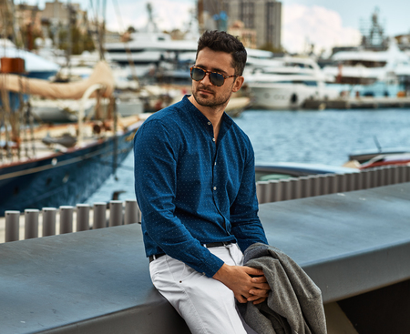 young handsome man in blue shirt wear sunglasses and relaxing in the port Stockfoto