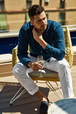 Handsome model relaxing and drinking white wine Stockfoto