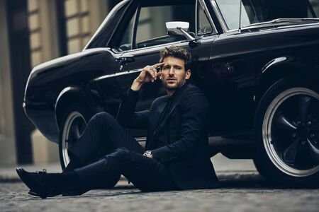Handsome man in black suit sitting on the street near his old classic car Imagens