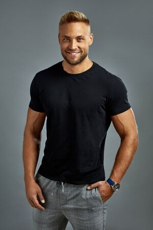 Sexy man in balck t-shirt looking at camera and smiling