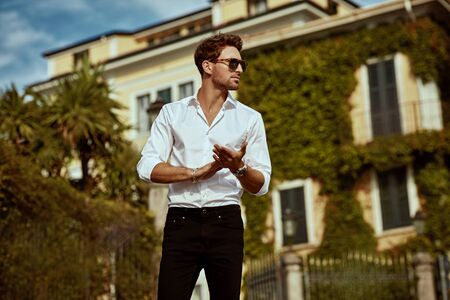 Handsome young man in sunglasses in front of luxury home villa