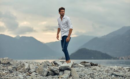Fashionable male model walking on the stony beach over alps mountain view