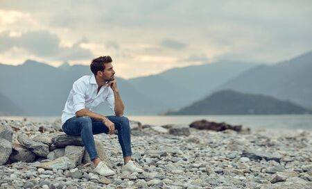 Fashionable male model relaxing on the stony beach