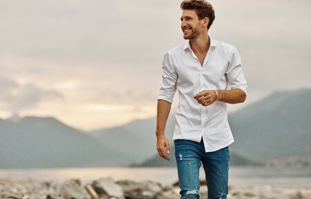 Smiling male model standing on a background of lake and mountains during the sunset