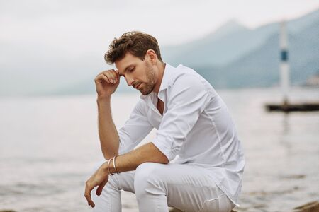 Handsome male model thinking outdoor on a background of lake and mountains