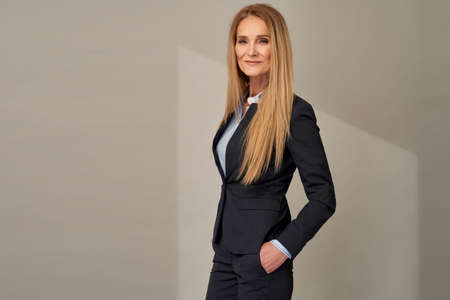 Portrait of adult woman with long blond hair posing in elegant suit over gray background in studio