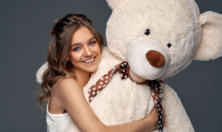 Beautiful cheerful young girl with big bear isolated on gray background