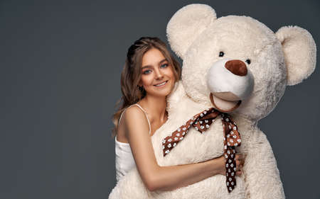 Beautiful cheerful young girl with cute big bear isolated on gray background Stockfoto