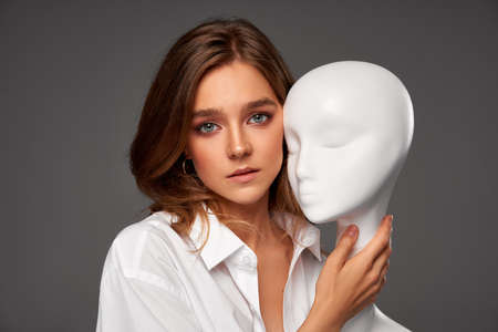 Portrait of young woman with mannequin face isolated on gray background Stockfoto