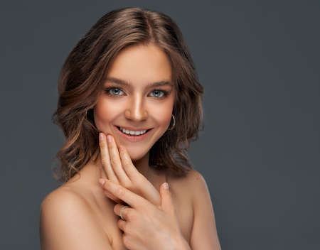 Portrait of cheerful young model with white teeth touchnig chin