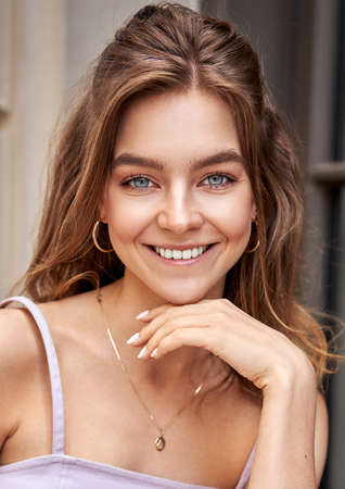 Portrait of beautiful smiling girl touching chin and looking at camera