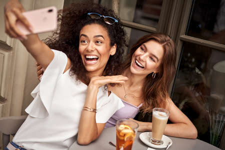 Pretty young girls with big smile having fun and taking selfie in cafe Stockfoto