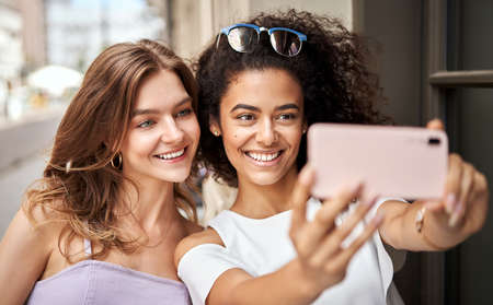 Pretty young girls with big smile having fun and taking selfie