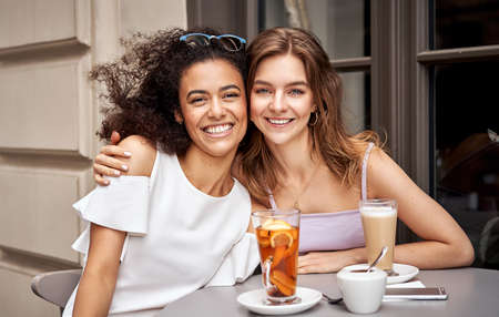 Pretty young girls smiling at the camera and having fun in cafe Stockfoto