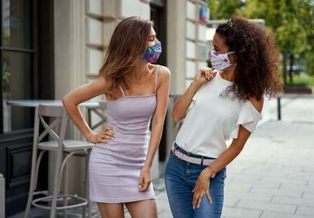 Two women walking down the street and talking with protective mask to protect Covid-19 virus