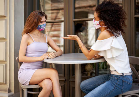 Couple friends in stylish mask talking in a cafe