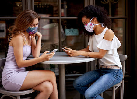 Two women in stylish masks sitting in a cafe and holding their mobile phones Stockfoto