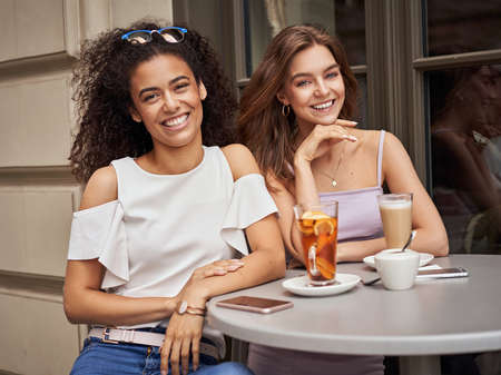 Pretty young girls smiling at the camera in cafe