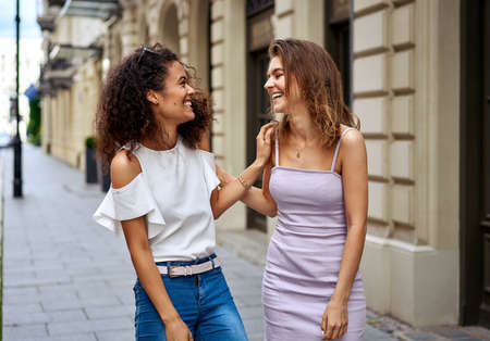 Two women are walking down the street and laughing
