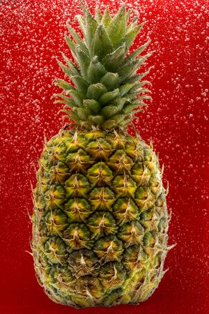 Pineapple under water covered with bubbles and with bubbles on the background red